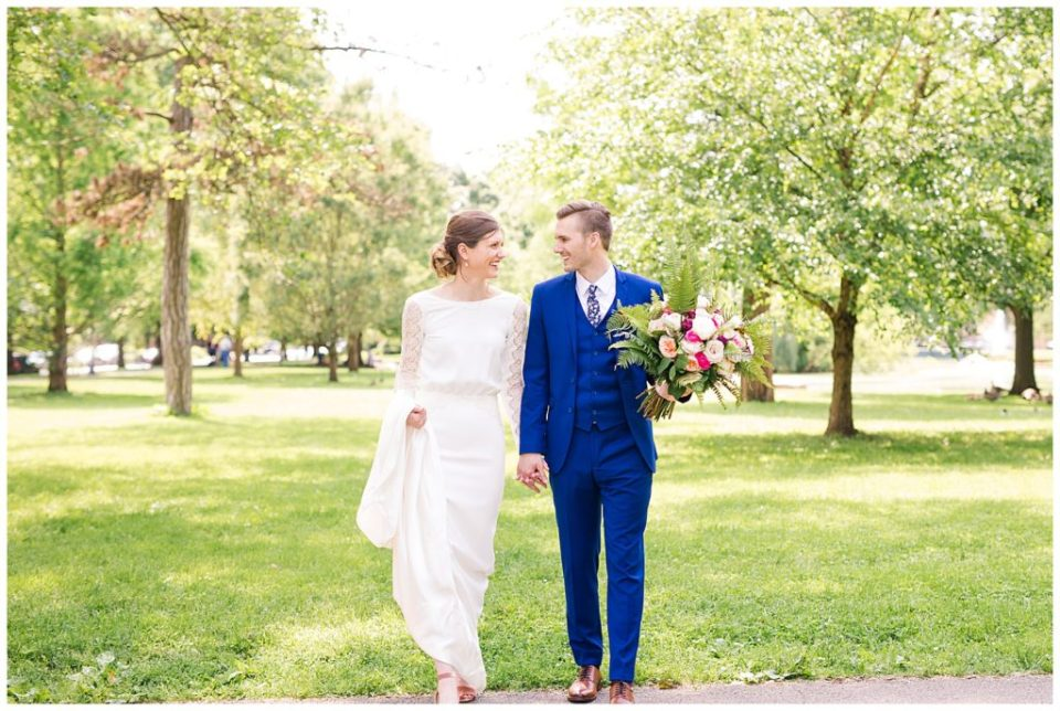 A picture of a bride and groom holding hands as they walk together outside, surrounded by trees at Dock 580 wedding venue  by Alayna Parker  - Columbus  wedding photography