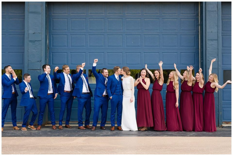 A picture of the bride and groom kissing as their wedding party cheers them on, lined up beside them at Dock 580 by Alayna Parker Photography  - Columbus  wedding pictures
