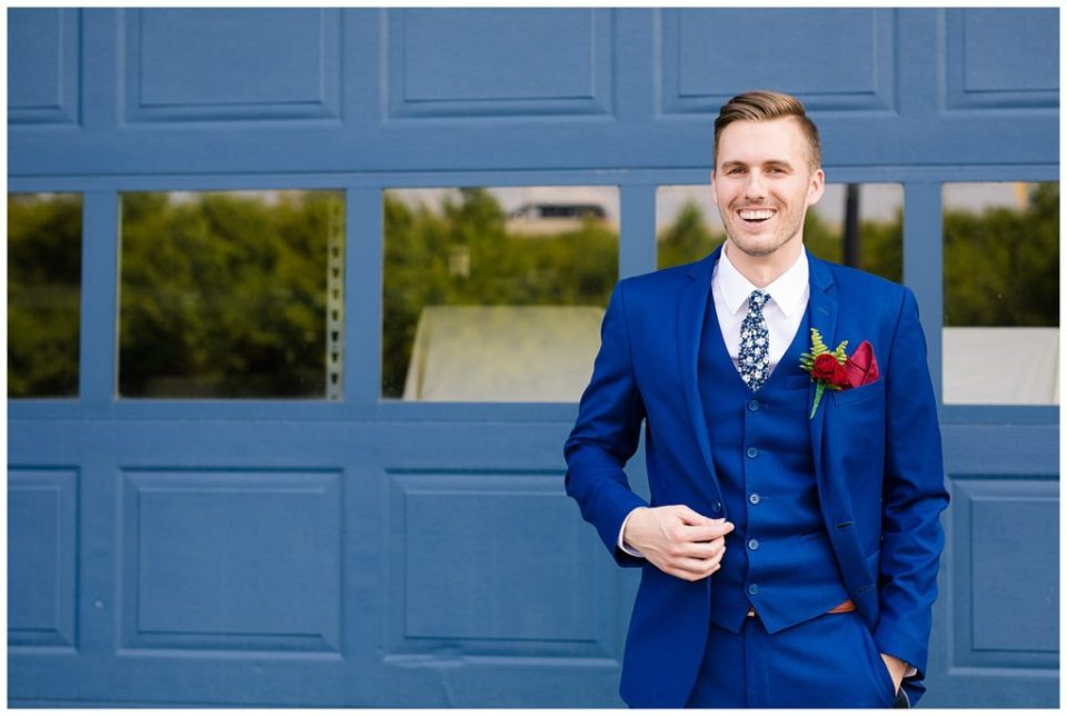 A photograph of a groom smiling in his blue tuxedo and boutonniere of red roses at Dock 580 wedding venue in downtown Columbus by Alayna Parker Photography  - Columbus OH marriage photography