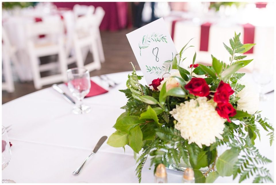 centerpieces with ferns, red flowers, and white flowers