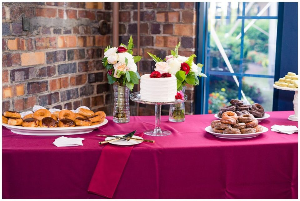 wedding dessert table with donuts, macaroons, and wedding cake