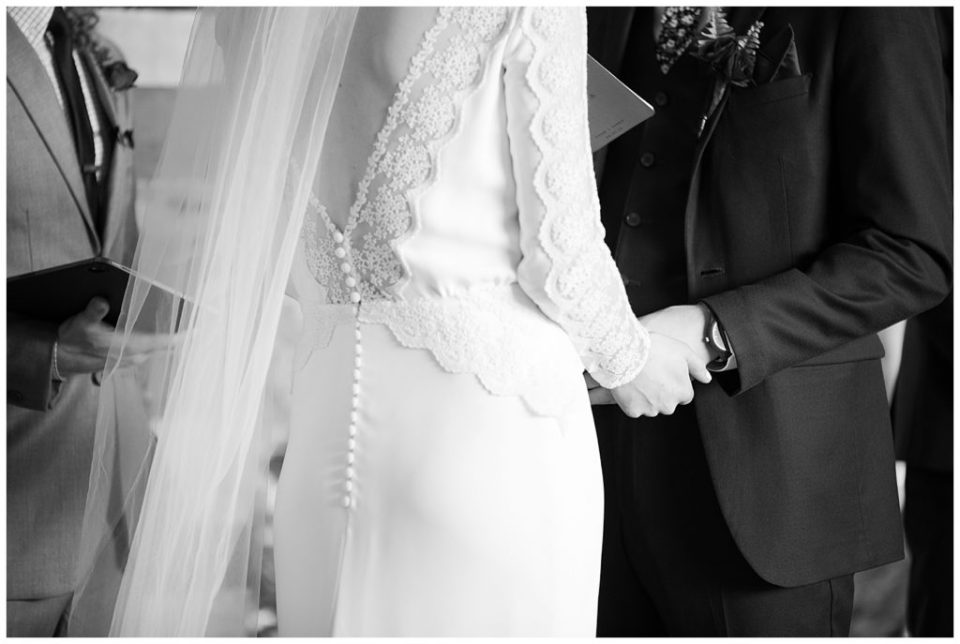 black and white image of bride and groom holding hands during wedding ceremony