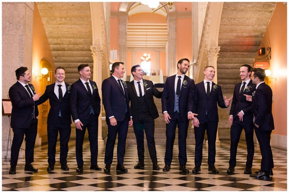 A photograph of the groom and his groomsmen relaxed and laughing together in their black tuxedos at an Ohio Statehouse wedding by Alayna Parker Photography  - Columbus OH wedding pictures