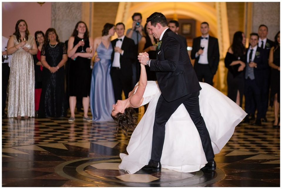 A photograph of a groom dipping his bride in their first dance at the wedding reception, surrounded by their guests at the Ohio Statehouse by Alayna Parker  - Columbus OH wedding photos
