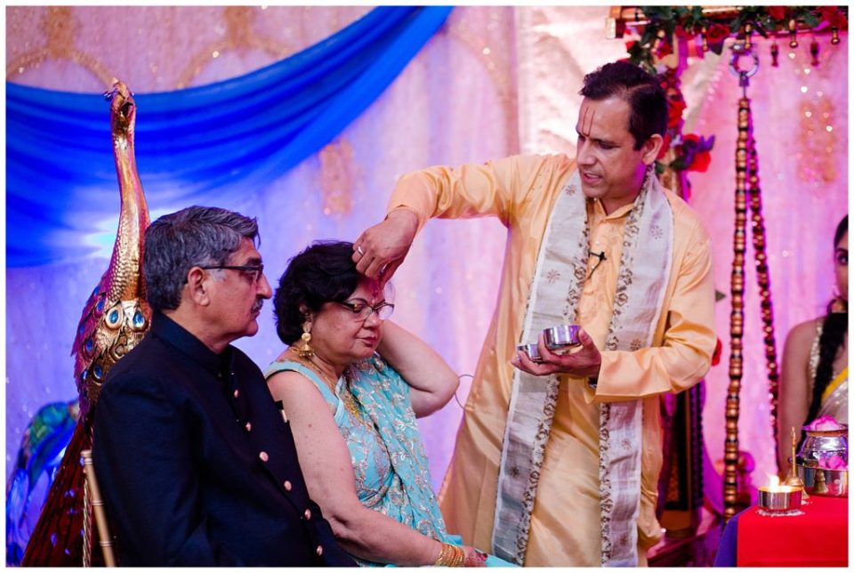 A picture of a Hindu priest applying red powder to the bride's mother's forehead at the engagement party at the Bertram Inn and Conference Center by Alayna Parker  - Akron  engagement photographers