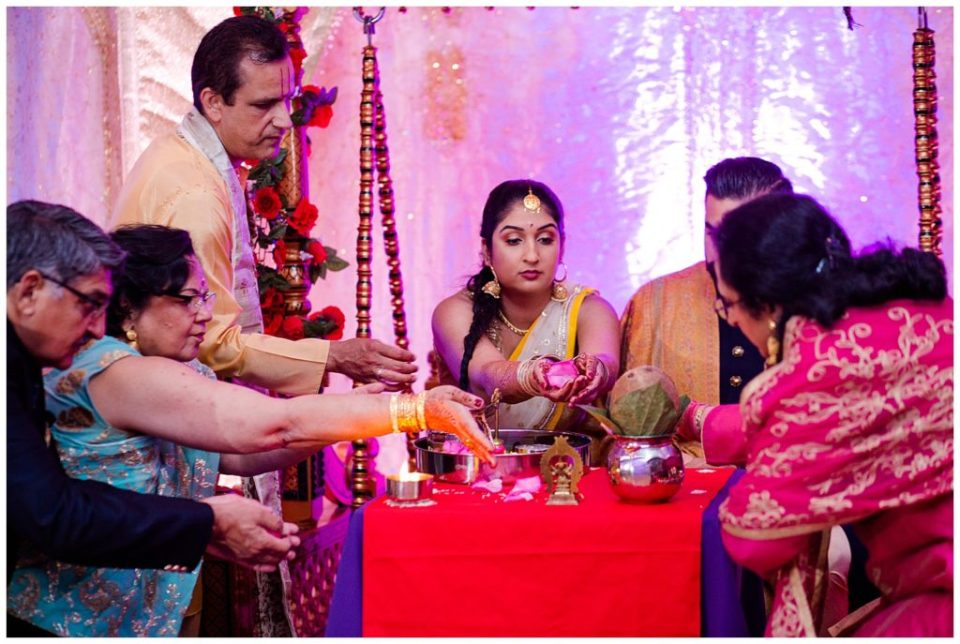 An image of the Hindu engaged couple and their parents performing traditional rituals along with the priest at their engagement ceremony at the Bertram Inn and Conference Center in Aurora by Alayna Parker  - Cleveland Ohio engagement photographer