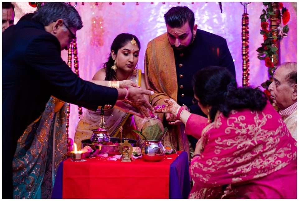 A picture of an engaged Hindu couple with their parents at each side performing traditional rituals at their engagement ceremony at the Bertram Inn wedding venue in Aurora, Ohio by Alayna Parker  - Cleveland  engagement photographers