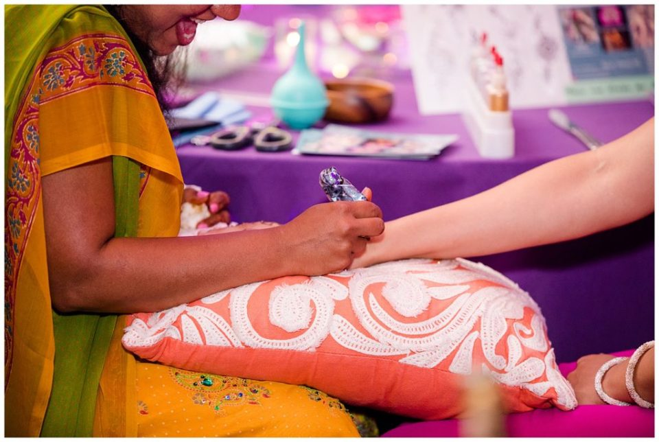 A photograph of a Henna artist decorating a guest's arm at a Hindu engagement party at the Bertram Inn and Conference Center by Alayna Parker  - Akron OH engagement photography