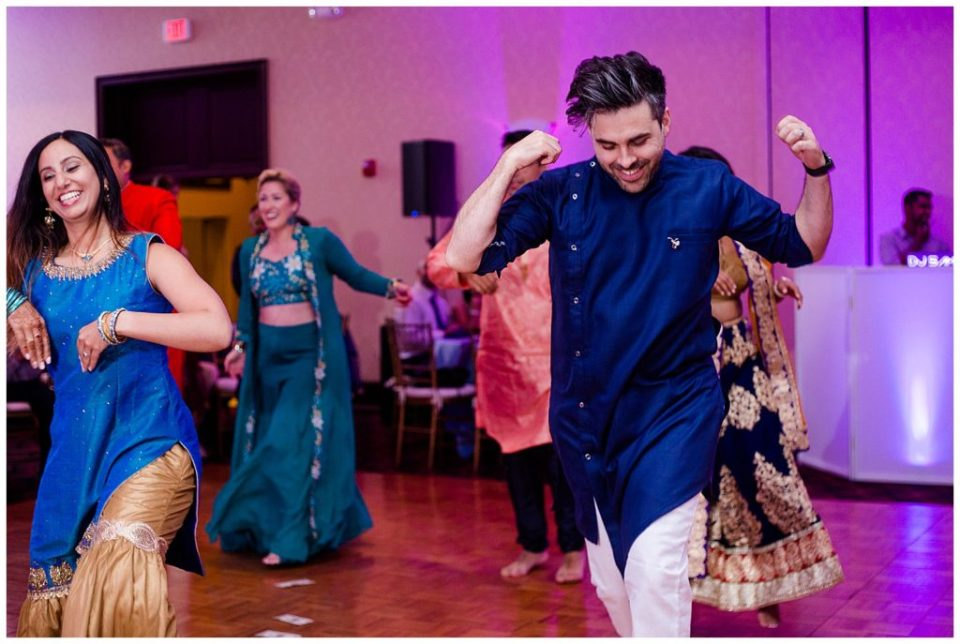 A picture of guests smiling and dancing at a Hindu engagement party at the Bertram Inn wedding venue in Aurora, Ohio by Alayna Parker Photography  - Cleveland  engagement photographers