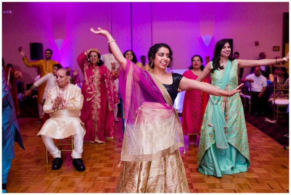 An image of guests performing traditional dances at a Hindu engagement celebration at the Bertram Inn and Conference Center by Alayna Parker Photography  - Akron Ohio engagement photographer
