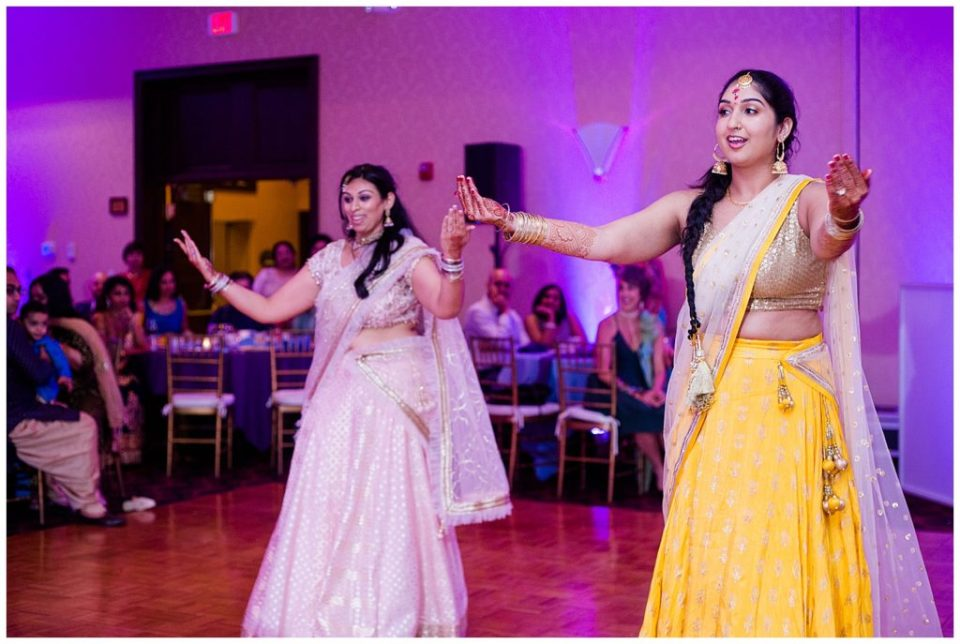 A photograph of an Indian bride and a friend performing a traditional dance at a Hindu engagement party at the Bertram Inn and Conference Center by Alayna Parker Photography  - Akron OH engagement photography
