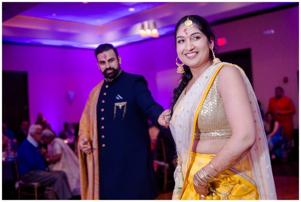 An image of an engaged Indian couple smiling and dancing together a the Hindu celebration of their engagement at the Bertram Inn wedding venue by Alayna Parker Photography  - Akron Ohio engagement photographer