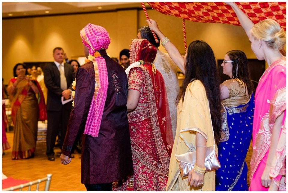 A picture of an Indian bride and her family and friends entering the Hindu temple under a canopy to begin the traditional wedding ceremony at the Bertram Inn and Conference Center by Alayna Parker Photography  - Akron  wedding photographers