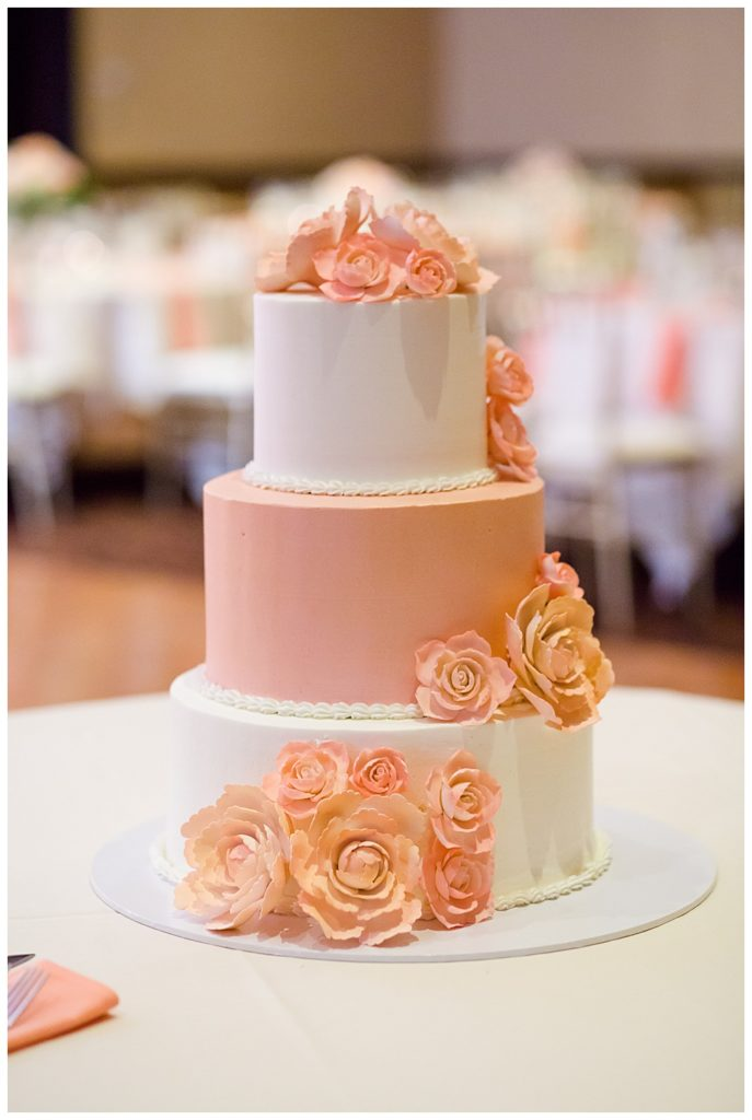 pink and white wedding cake with pink icing flowers