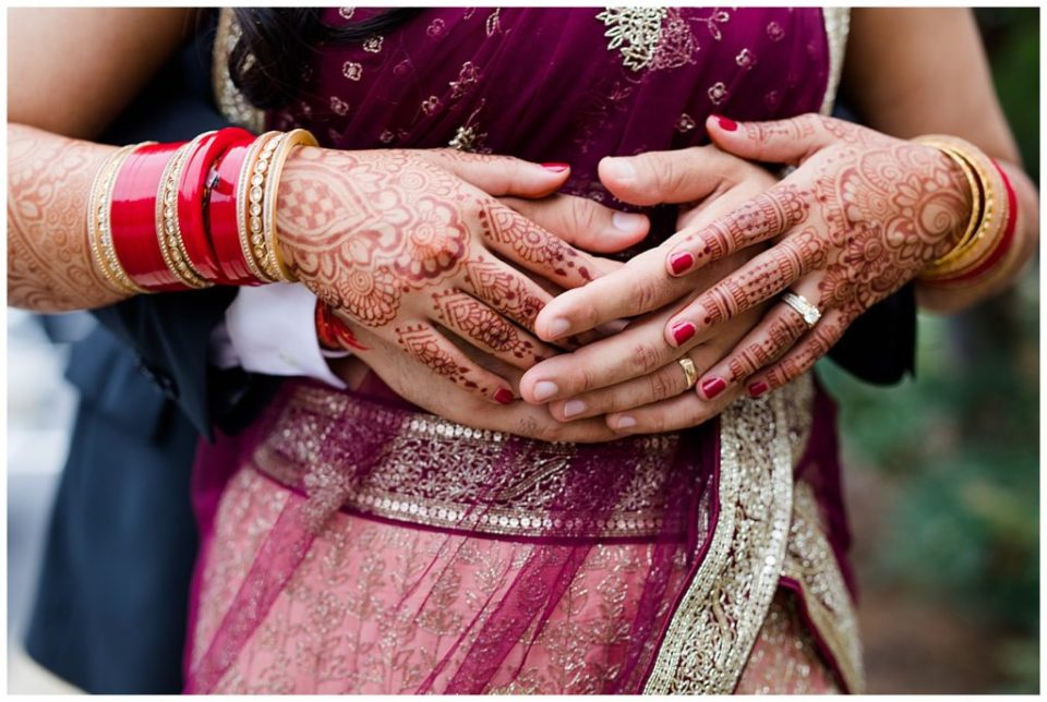 close up of bride and groom's rings with henna tattoos