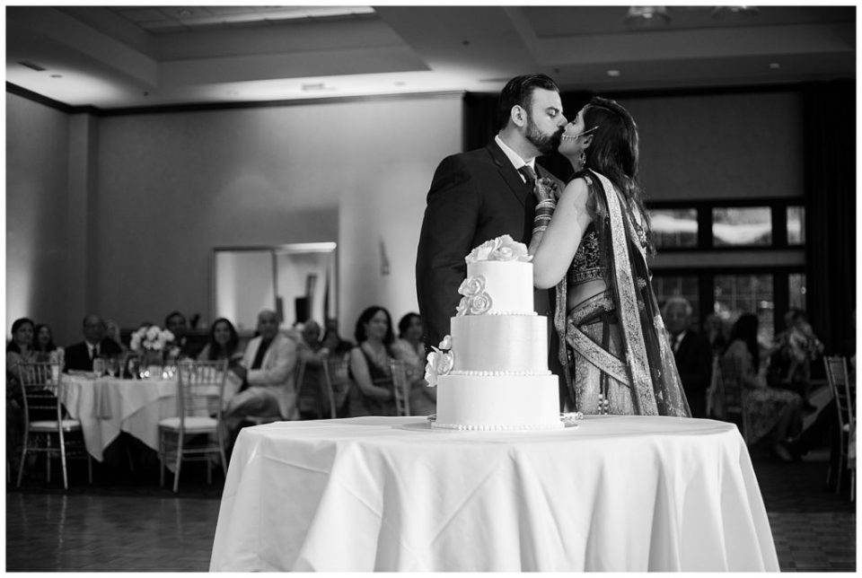 black and white image of bride and groom kissing after cutting cake at bertram inn