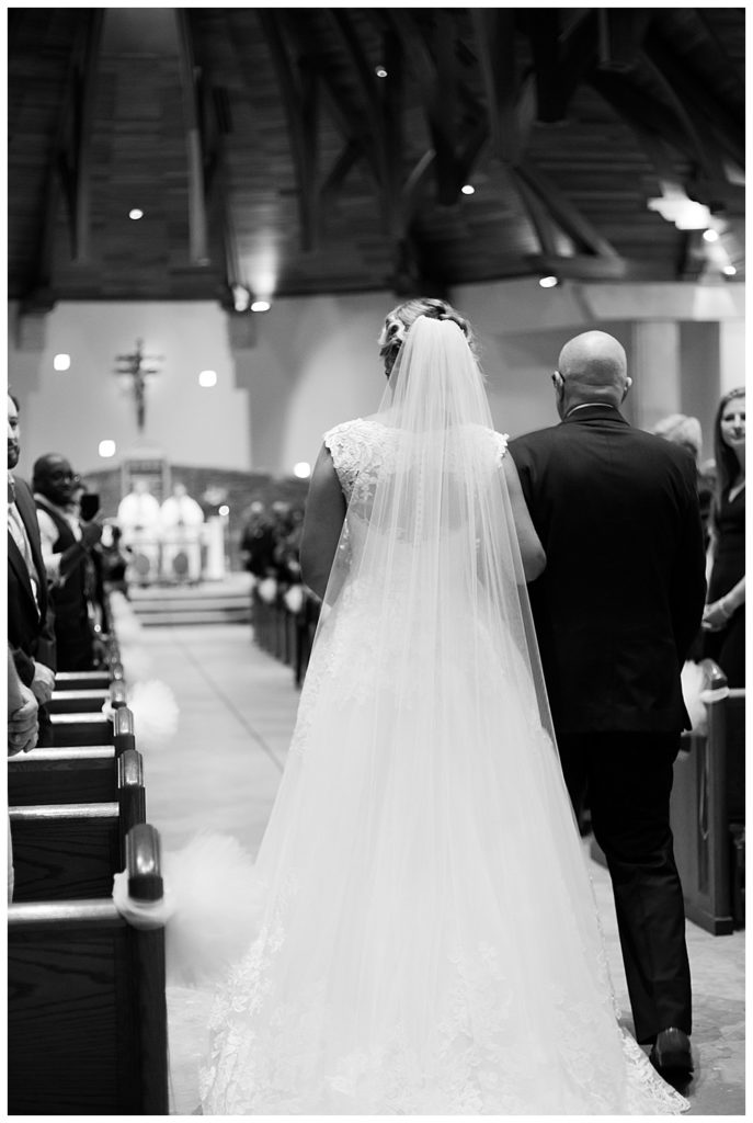 A photograph in black and white of the bride and her father walking down the aisle in church toward the groom as the wedding ceremony begins  by Alayna Parker  -   wedding photographer in Columbus