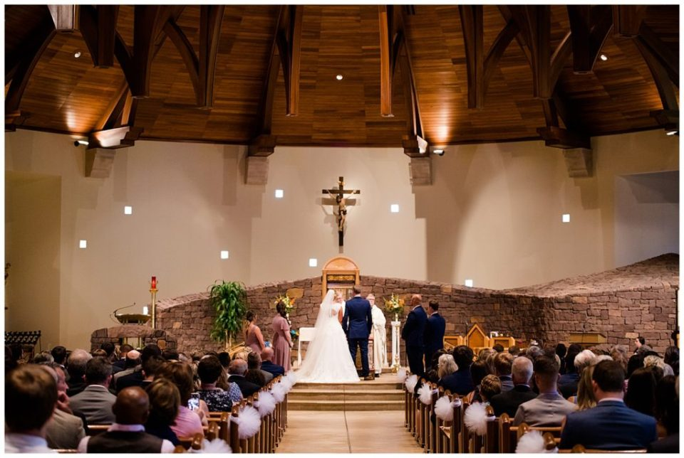 A photograph of a long-range view of the bride and groom standing before the officiant in church during the wedding ceremony, as the audience looks on  by Alayna Parker  -   wedding photographers in Columbus Ohio