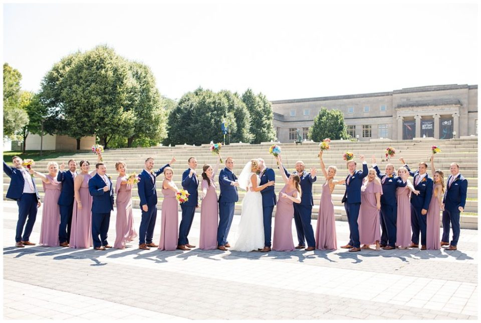 bridal party cheering while bride and groom kiss in front of steps at cosi