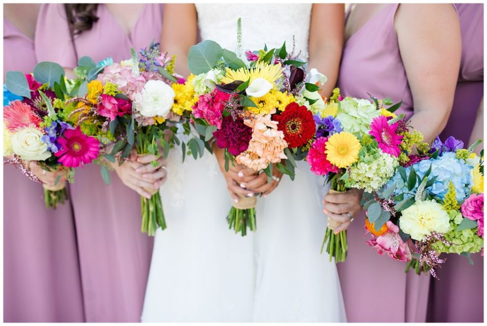 bride and bridesmaids holding colorful bouquets