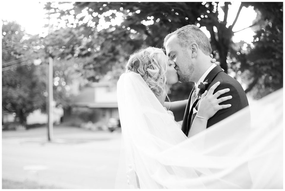black and white image of bride and groom kissing while veil blows in wind