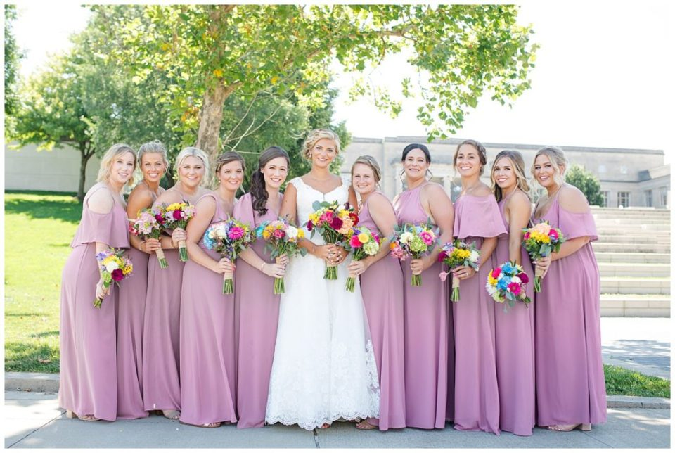 bride and bridesmaids smiling at camera in front of steps at cosi