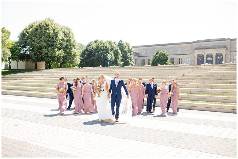 bride and groom walking while bridal party walks behind them in front of steps at cosi