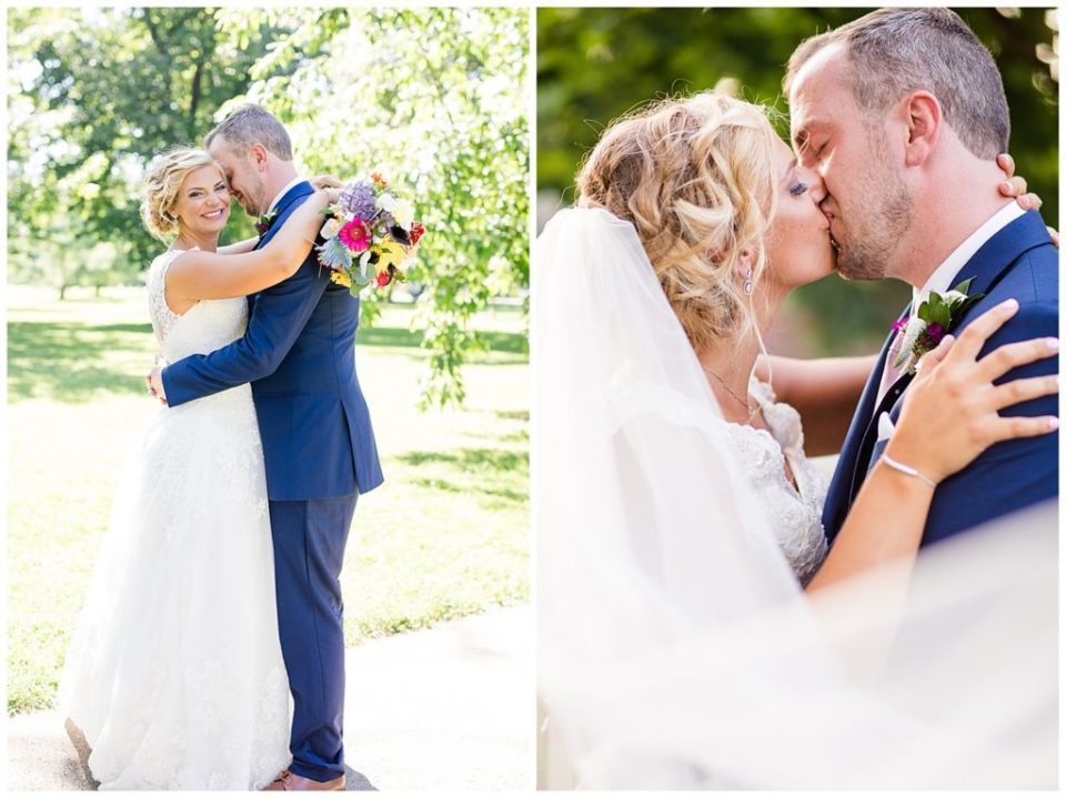 bride and groom kissing while veil blows in wind