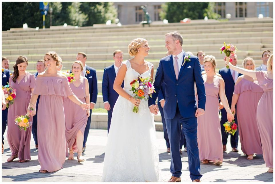 bride and groom laughing at each other while bridal party walks in background in front of steps at cosi
