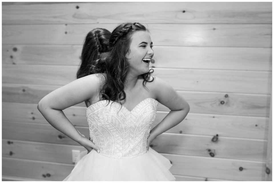 A picture in black and white of the bride laughing as her mother finishes buttoning up her wedding dress at the Cedar Grove Lodge venue in Hocking Hills, Ohio by Columbus  wedding photographer, Alayna Parker Photography
