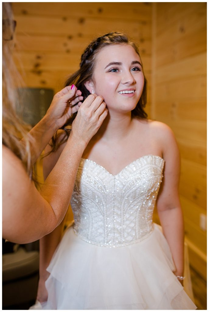 An image of the bride with her mother helping to put on her earrings as she finishes dressing for the wedding ceremony at the Cedar Grove Lodge wedding venue by Columbus Ohio wedding photographer, Alayna Parker Photography