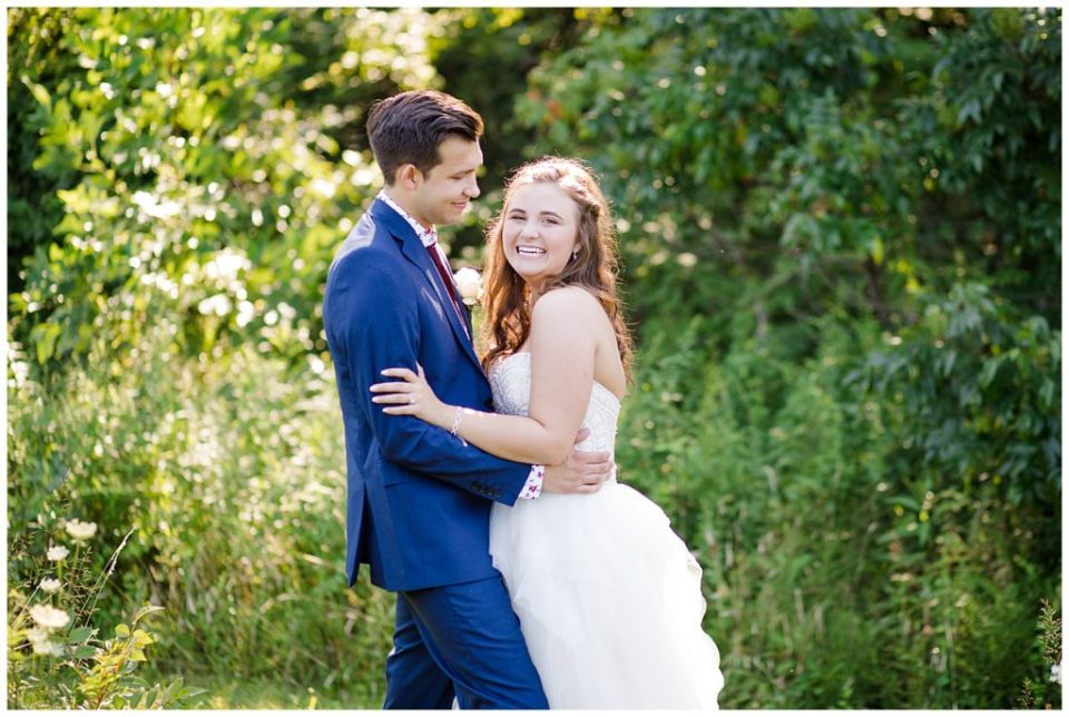 bride laughing at camera while groom looks at her