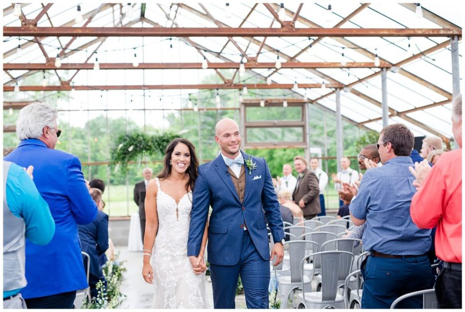 A photograph of the bride and groom walking down the aisle after their wedding ceremony, smiling as the guests clap at the Oak Grove wedding venue by Columbus OH wedding photographer, Alayna Parker Photography