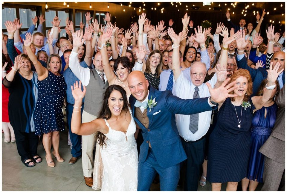 bride and groom take large group photo with guests on the dance floor at jorgensen farms oak grove