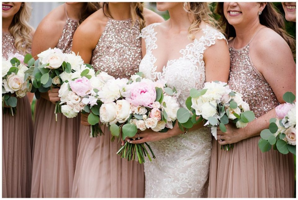 A picture of a closeup of the bouquets of a bride and her bridesmaids as they are lined up together at Jorgensen Farms wedding venue by Alayna Parker  - Columbus  rustic wedding photography