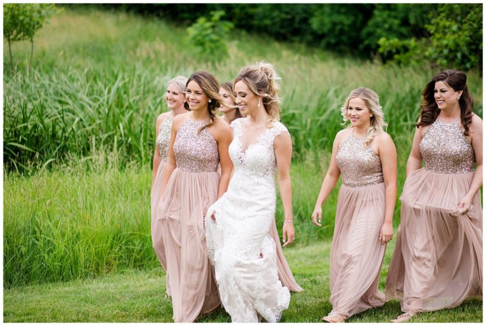 A photograph of a bride and bridesmaids walking together outdoors, relaxing together before the wedding at Jorgensen Farms wedding venue by Alayna Parker Photography  - Columbus OH outdoor wedding photographer