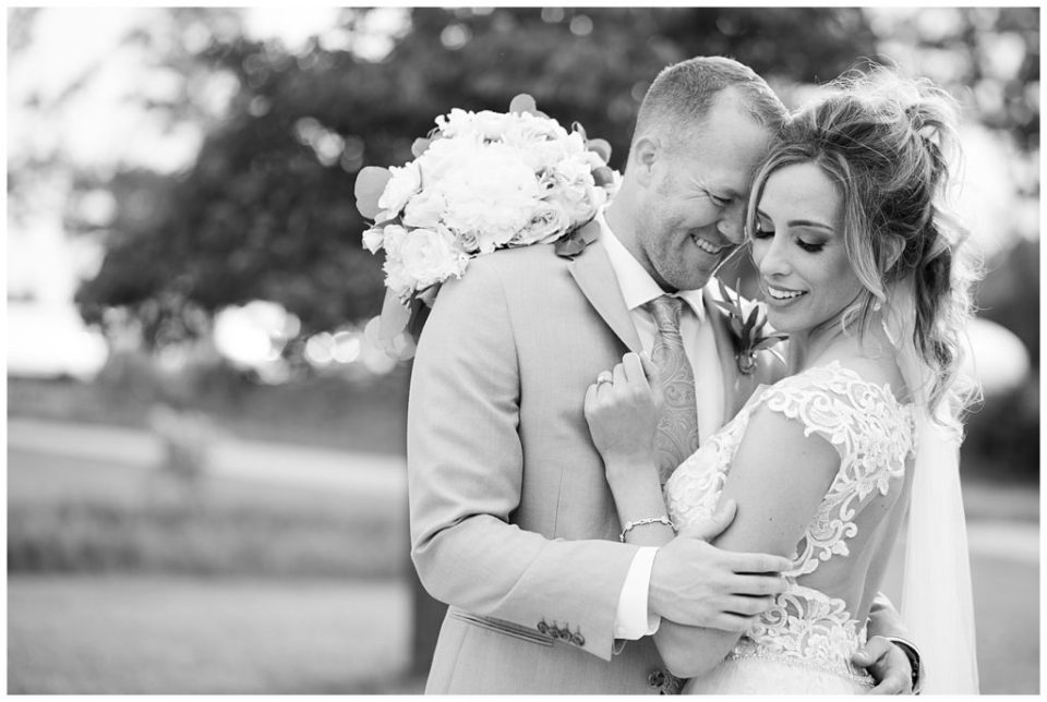 A photograph in black and white of a bride and groom holding each other, tenderly touching foreheads at Jorgensen Farms wedding venue by Alayna Parker Photography  - Columbus OH wedding photographers