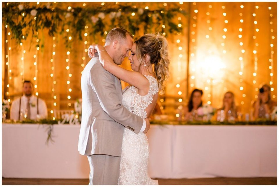 An image of the bride and groom romantically holding each other during their first dance at the wedding reception at Jorgensen Farms wedding venue by Alayna Parker Photography  - Columbus Ohio wedding photographer