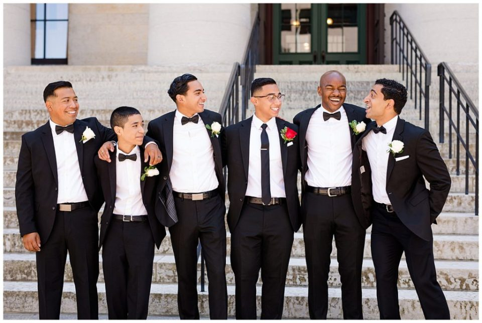 groom and groomsmen laughing with arms around each other at ohio statehouse