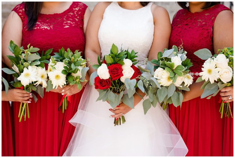 bridesmaids hold bouquets of white and green flowers and bride holds bouquet of with red and white roses