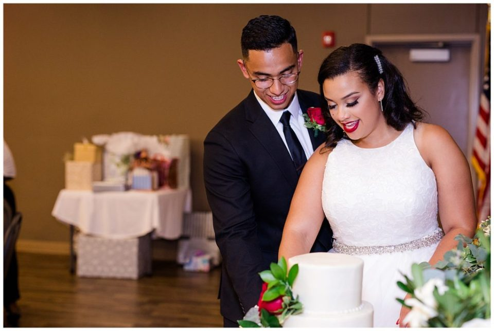 An image of the bride and groom smiling and cutting their wedding cake together by Columbus Ohio wedding photography specialist, Alayna Parker Photography