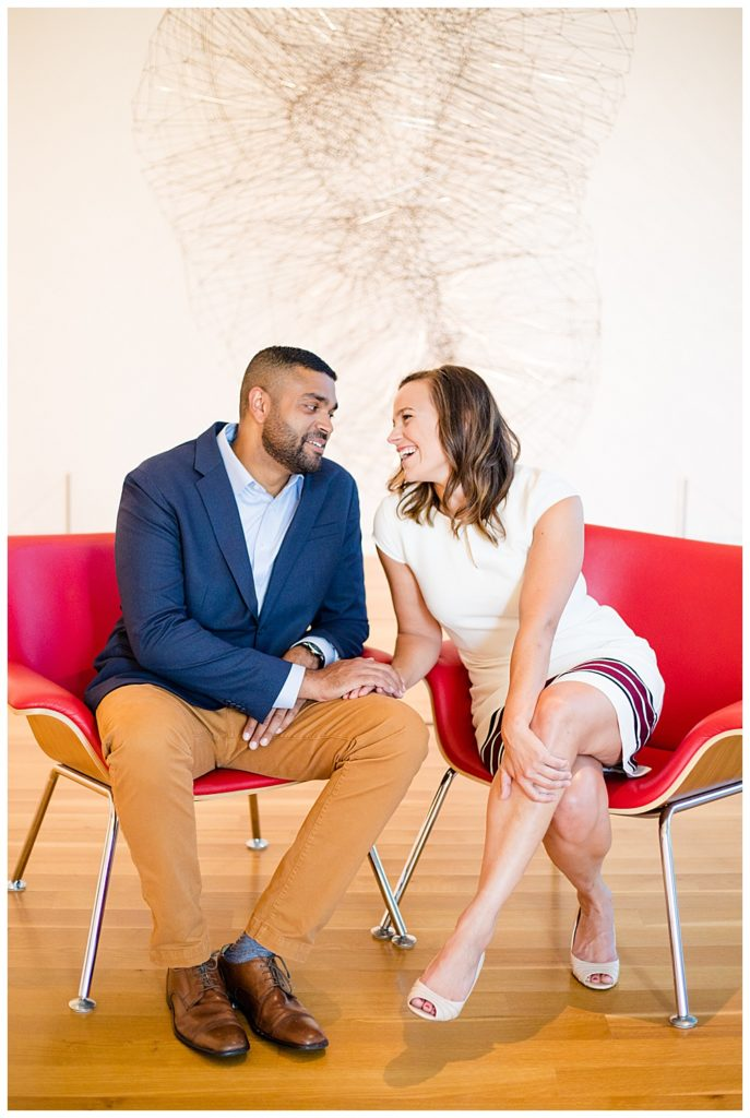 A photograph of an engaged couple sitting in an art museum, holding hands and romantically smiling at each other at the Columbus Museum of Art by Alayna Parker Photography Columbus OH engagement photography