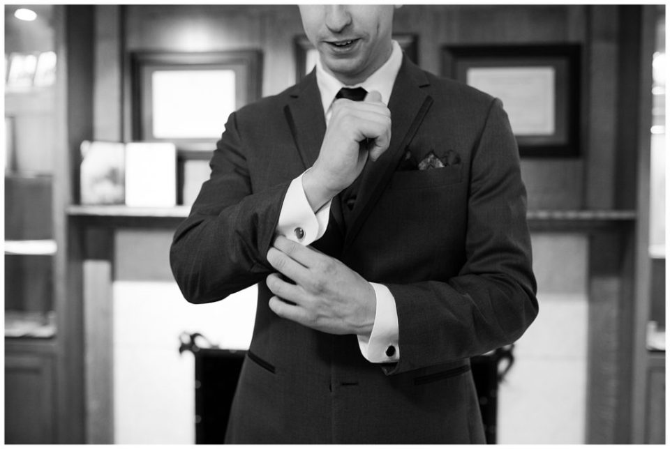 black and white image of groom putting on cuff links at station 67