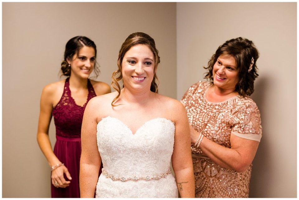 bride smiling after she gets wedding dress on at station 67