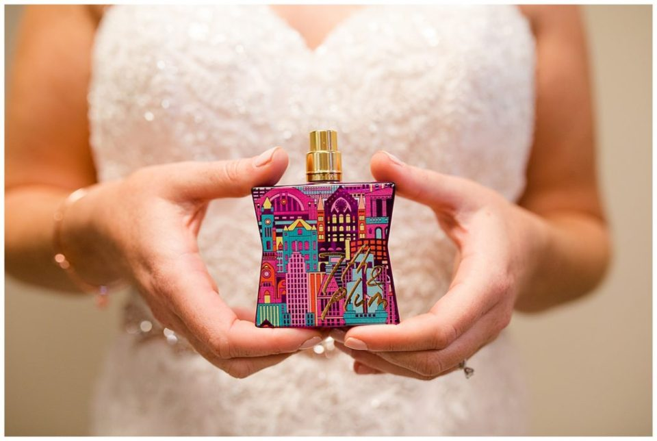 bride holding colorful bottle of perfume at station 67