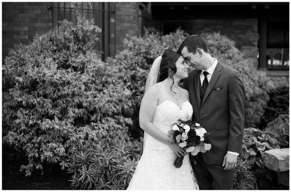 black and white image of bride and groom touching foreheads at station 67