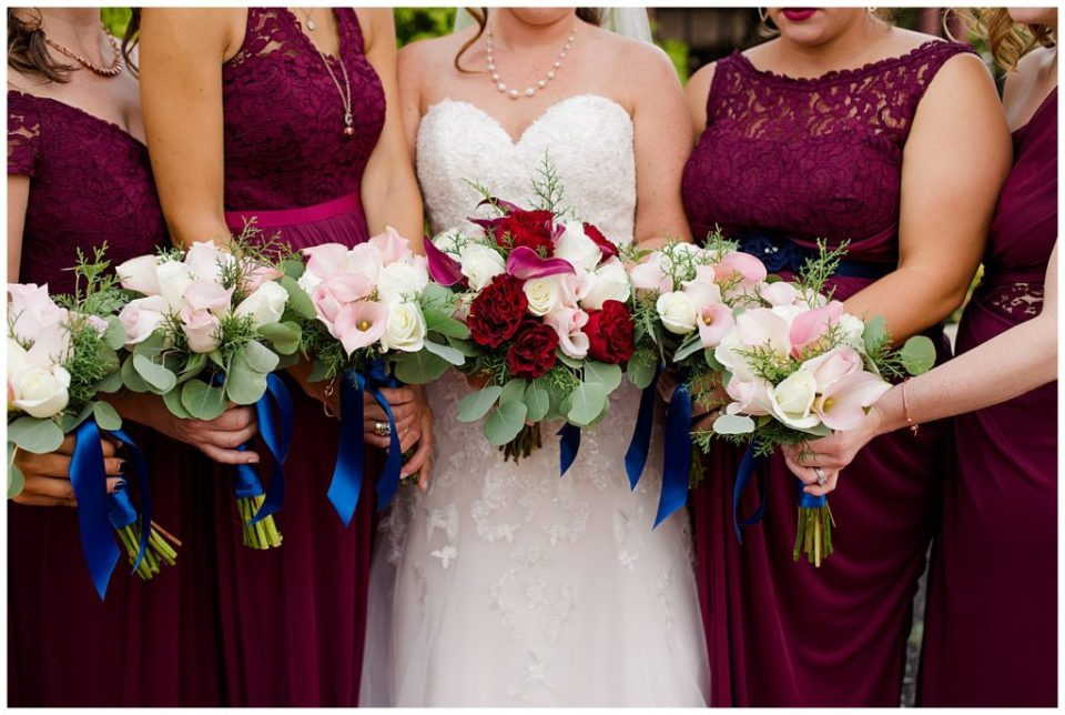 bride and bridesmaids hold bouquets of white and pink flowers at station 67