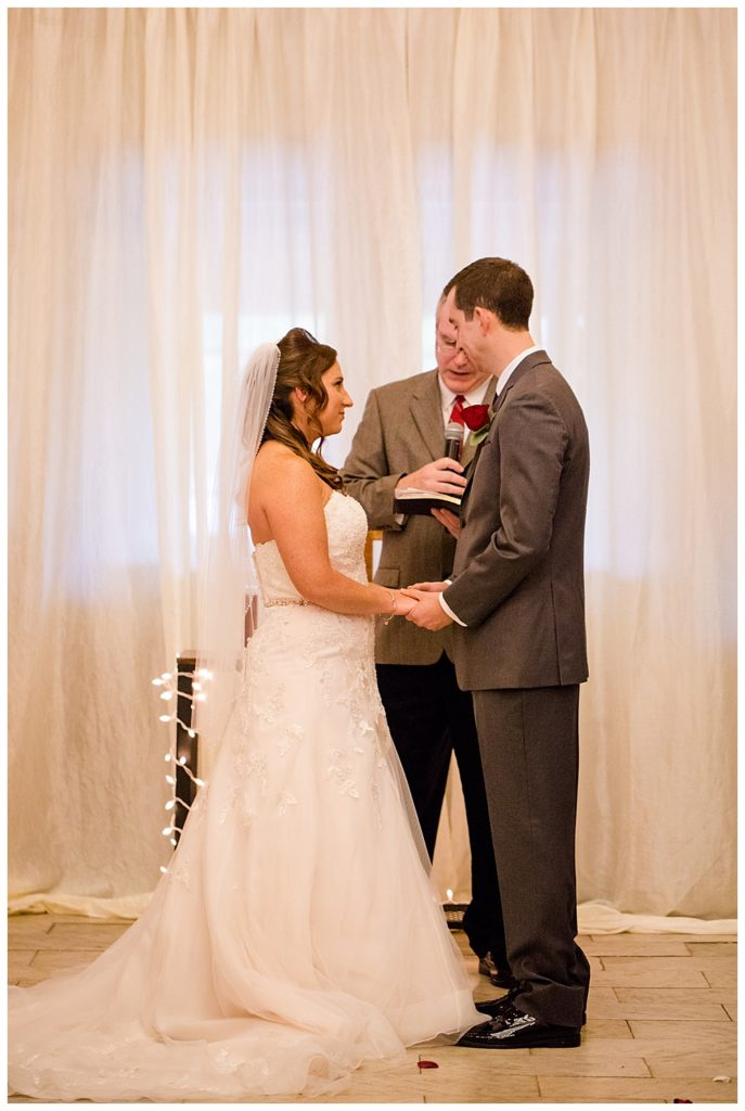 bride and groom standing in front of white curtain at station 67