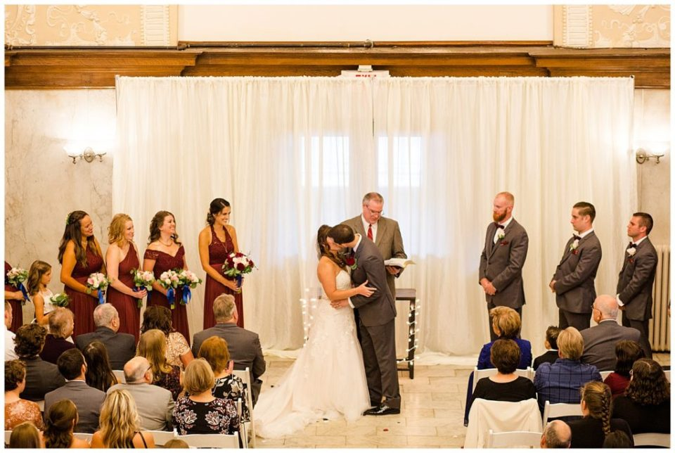 A photograph of a bride and groom at their wedding ceremony, kissing after the vows while the wedding party looks on at a Station 67 Columbus Ohio wedding by Alayna Parker Photography