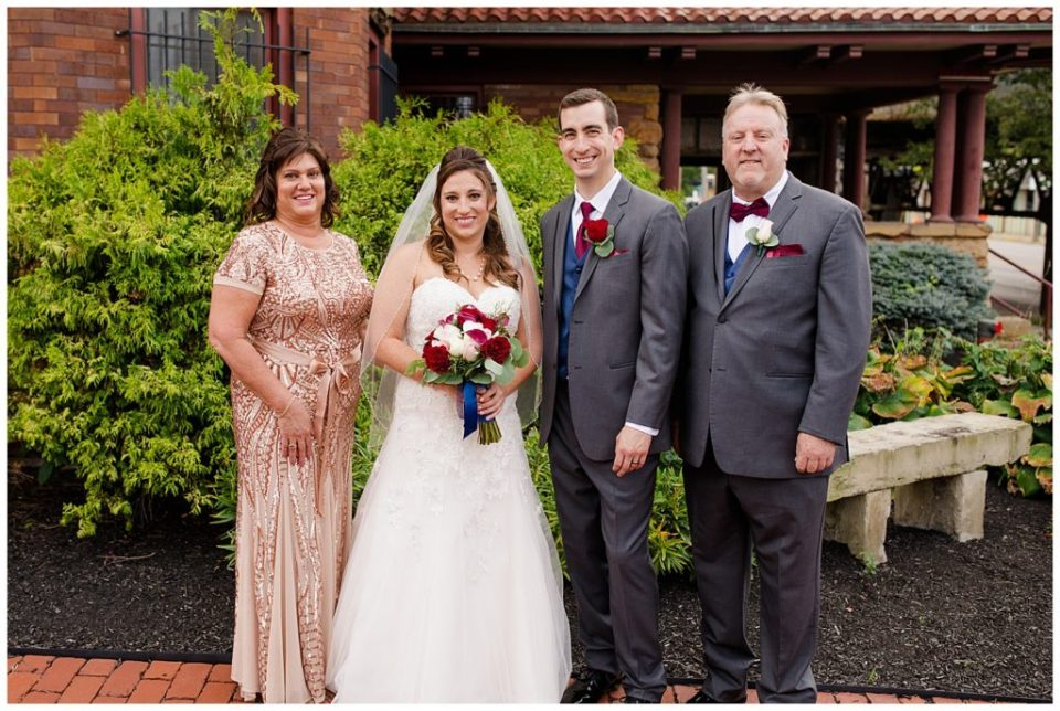 An image of the bride and groom standing with the bride's parents after the wedding ceremony at a Station 67 Columbus  wedding by Alayna Parker Photography